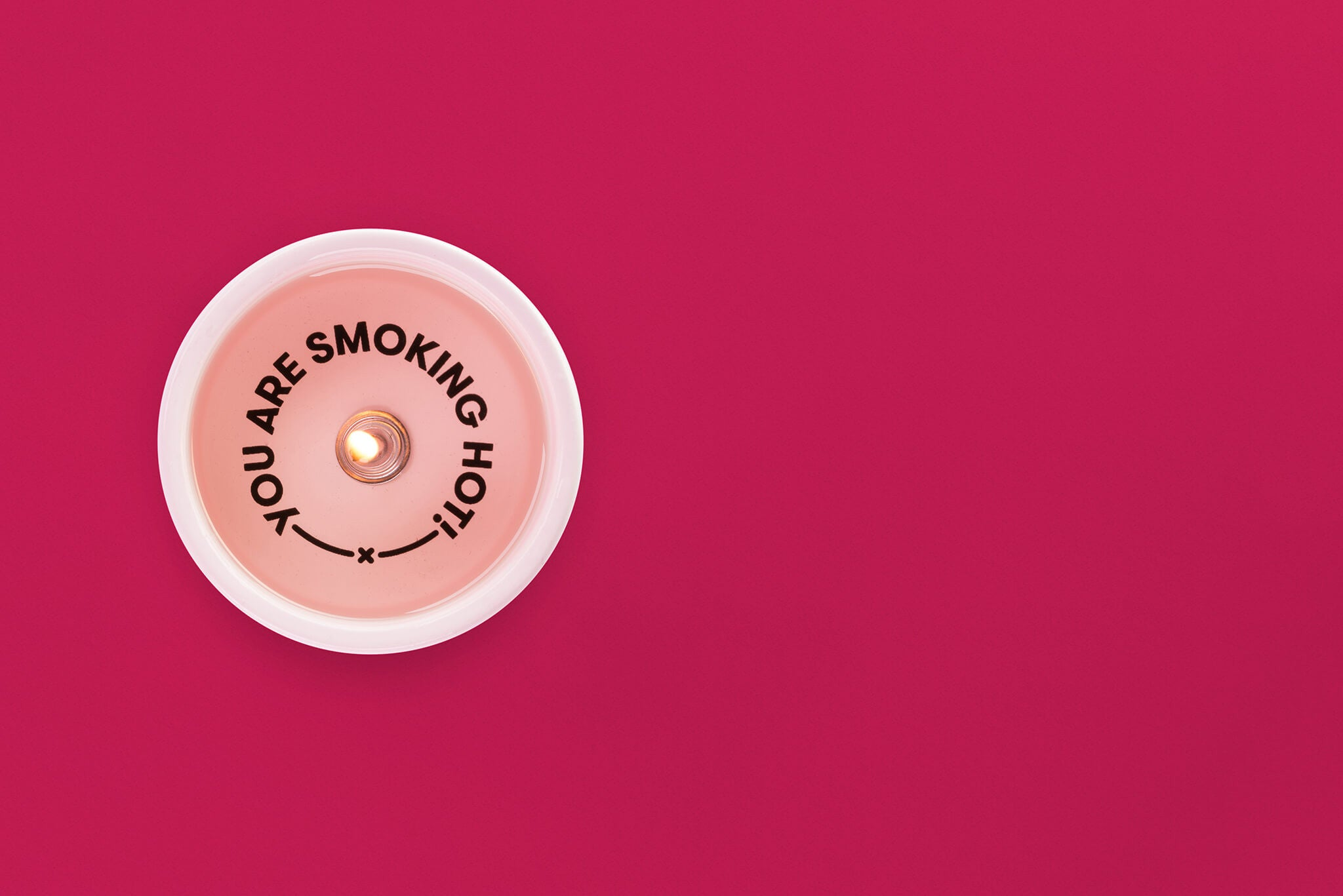 "Top view of ""I just wanted to tell you that you are smoking hot"" message candle with pink background."