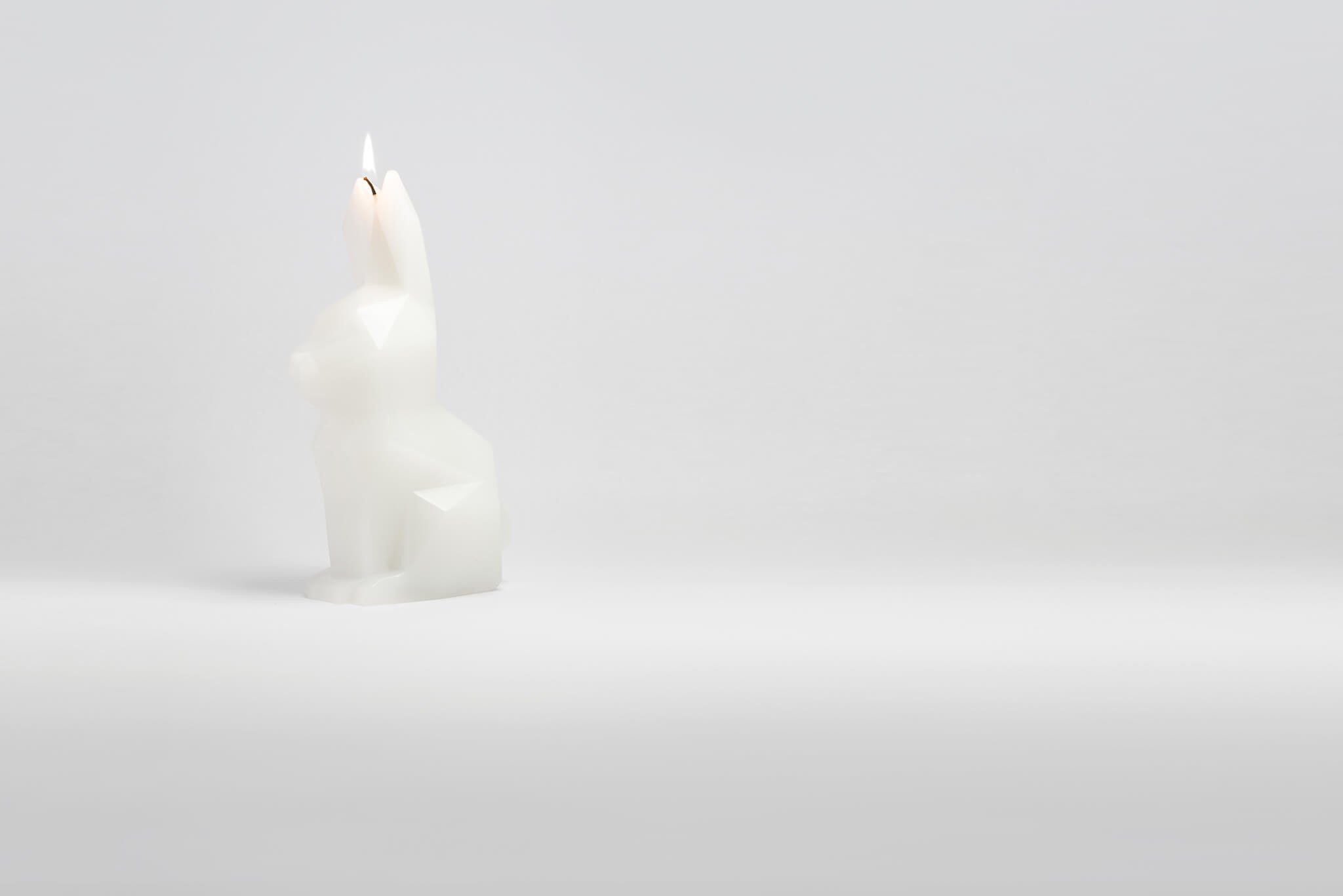 Side view of white hoppa bunny candle. Her wick has just been lit.
