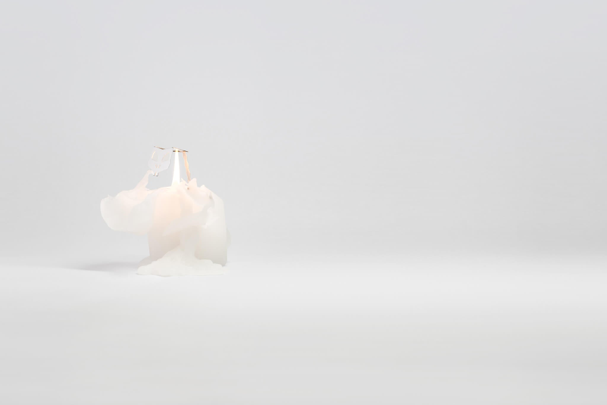 A burning white bunny candle reveals inner skeleton frame as the wax melts.