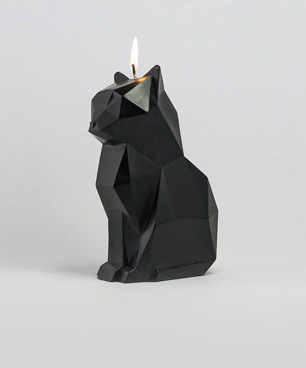 Side view of black kisa the cat candle with a lit wick.