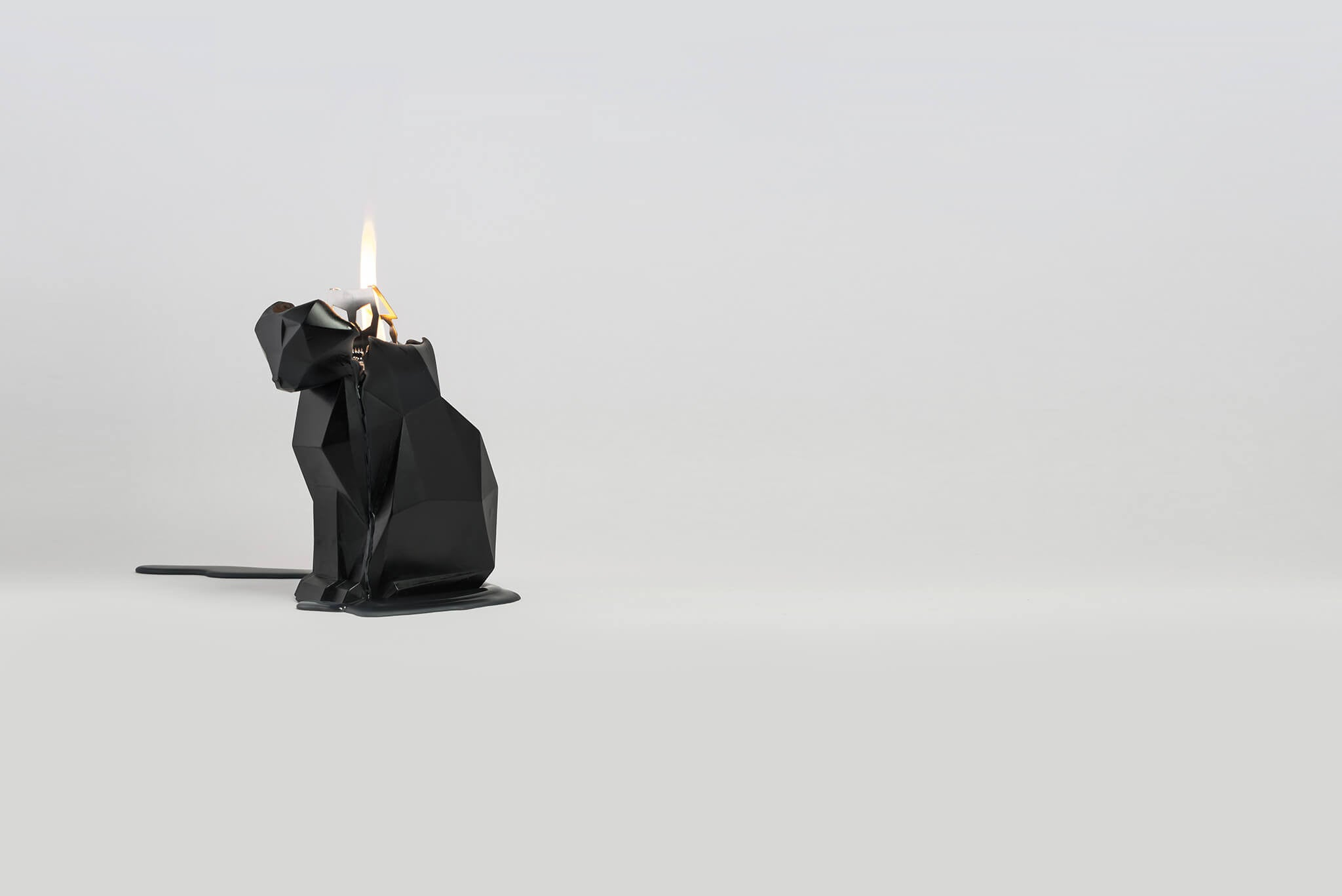 Side view of black kisa the cat shaped candle burning to reveal secret metal skeleton.