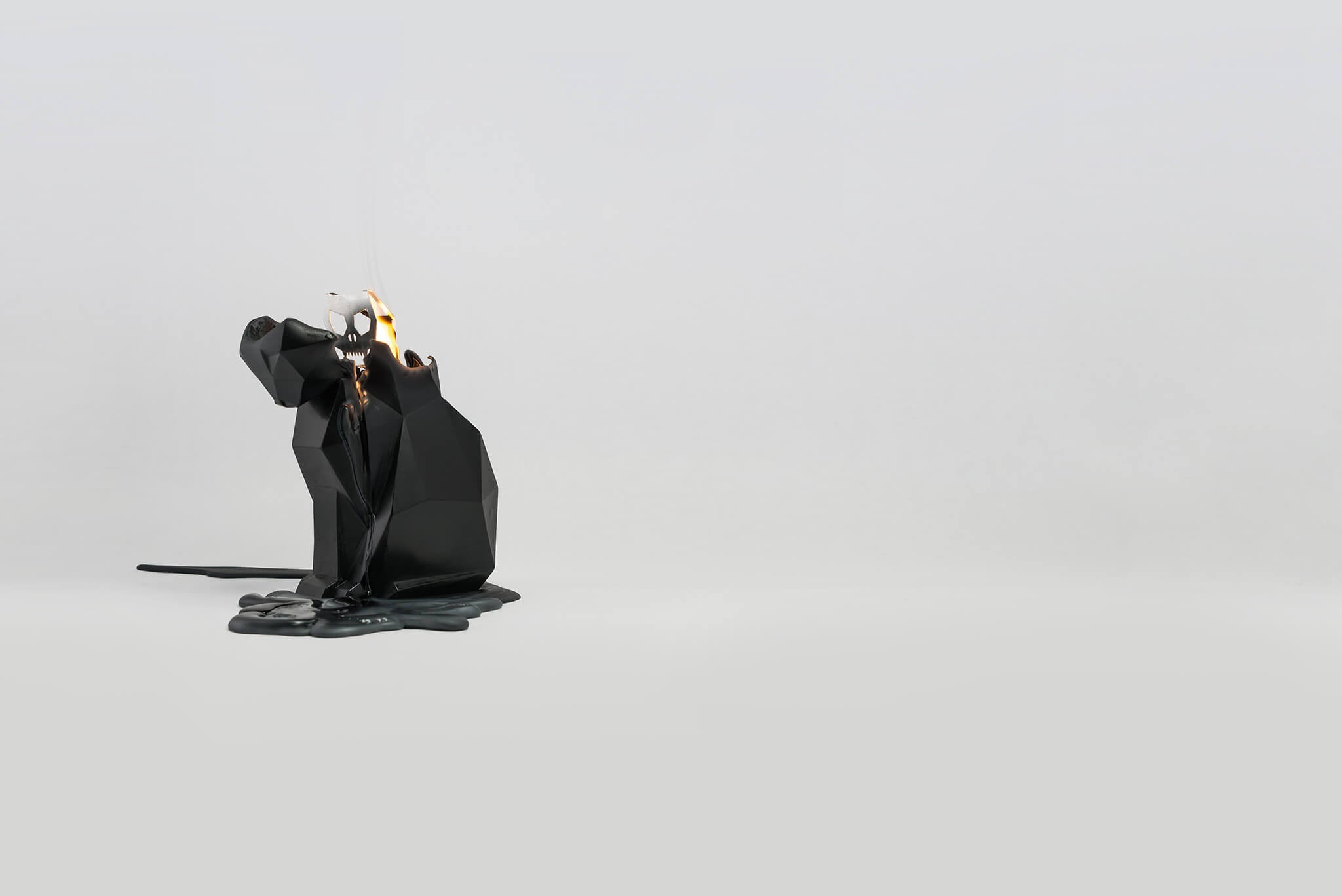 Side view of a melting black kisa the cat shaped pyropet candle.