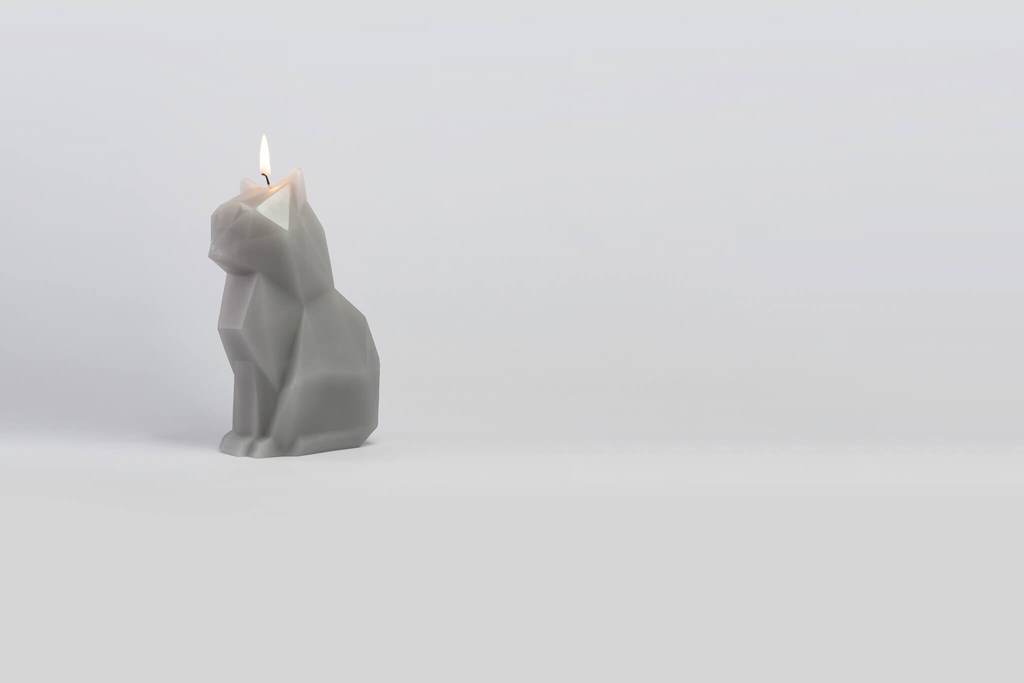 Side view of lit grey kisa the cat pyropet candle. The perfect cat gift for cat lovers.