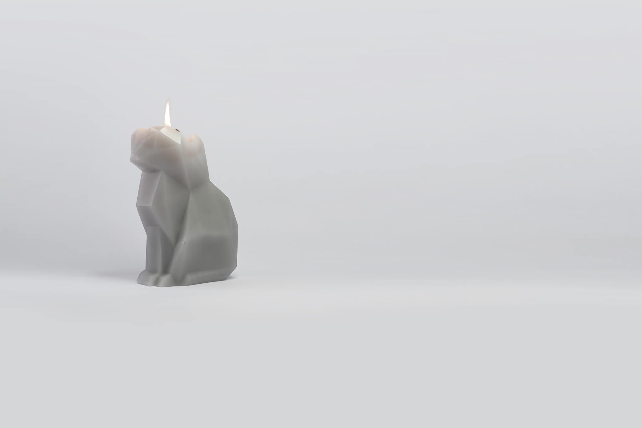 Side view of grey kisa the cat pyropet candle. As the wick burns she reveals a skeleton frame.