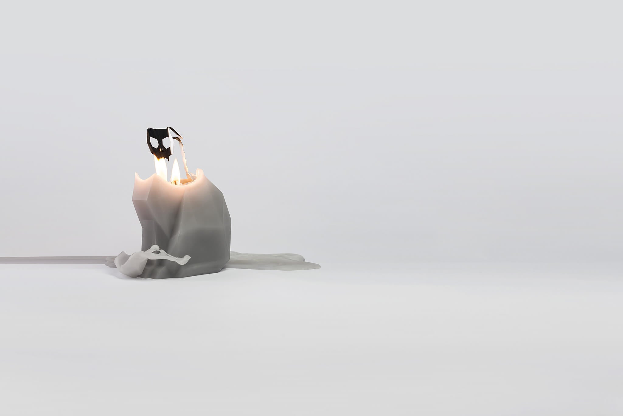 A melting grey kisa the cat pyropet reveals inner skeleton frame as the wax melts the candle.