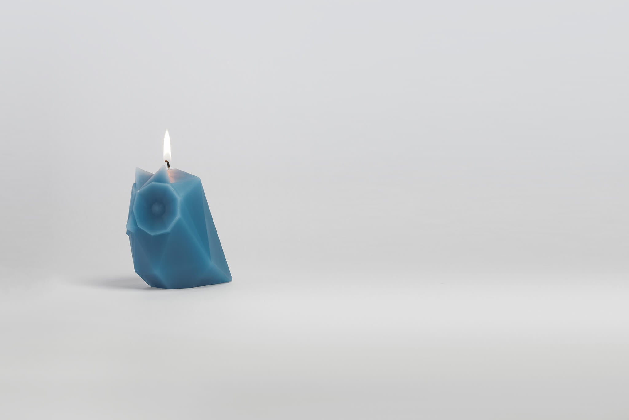 Side view of lit blue owl shaped candle.