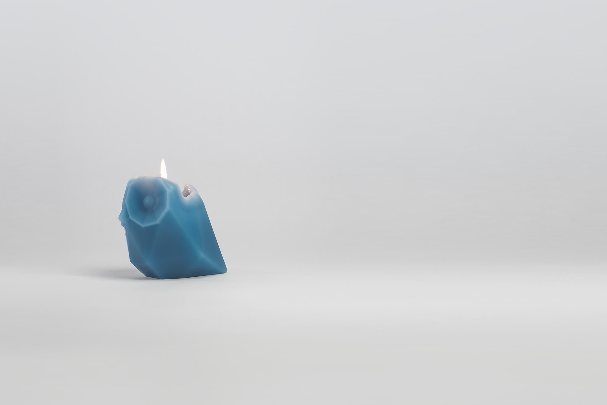 Side view of melting blue owl shaped pyropet candle.