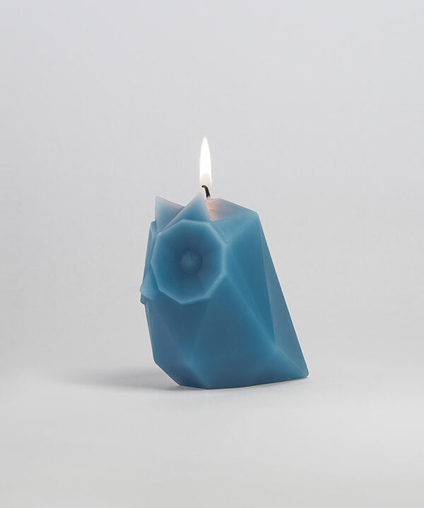 Side view of grey blue the owl shaped pyropet candle with wick burning.
