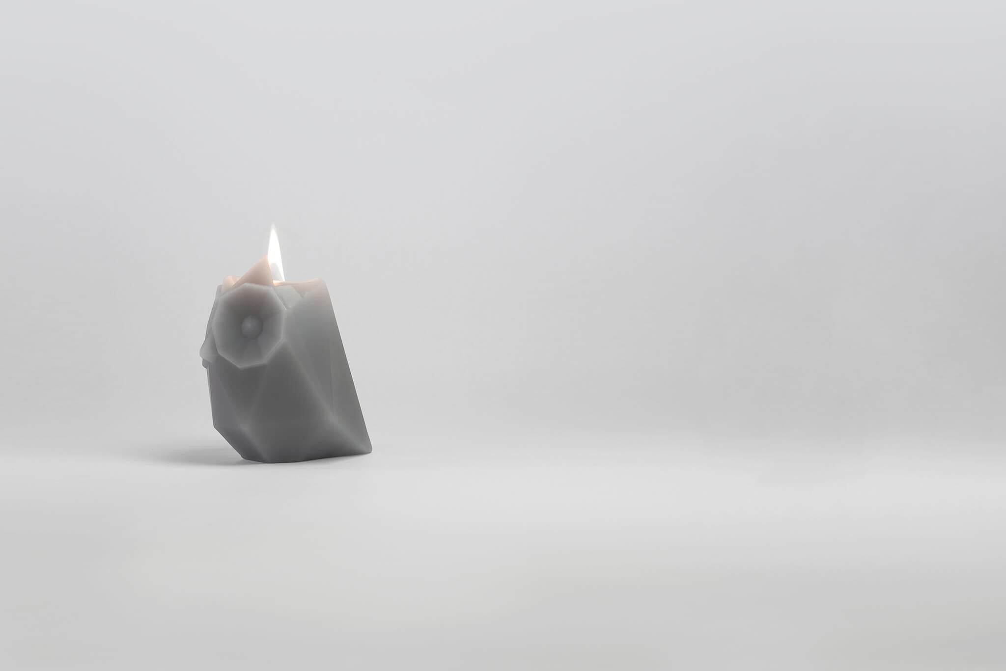 Side view of grey ugla the owl shaped pyropet candle with wick burning.