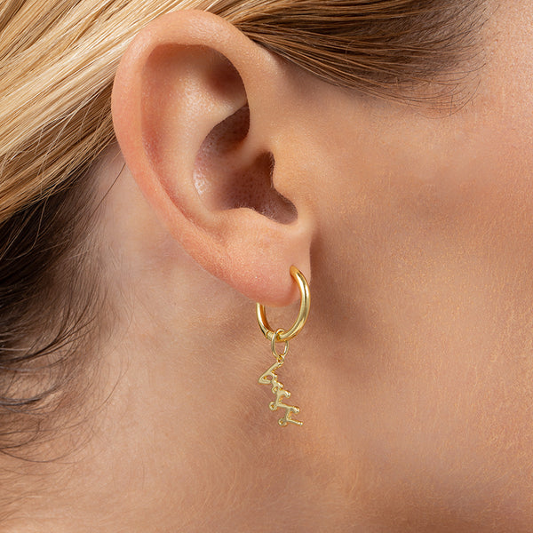 "Model wearing hoop earring with charm that says ""boss"" with 14k gold plating"