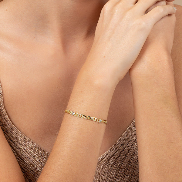 Model wearing 14k gold-plated curb chain bracelet with round cubic zirconia