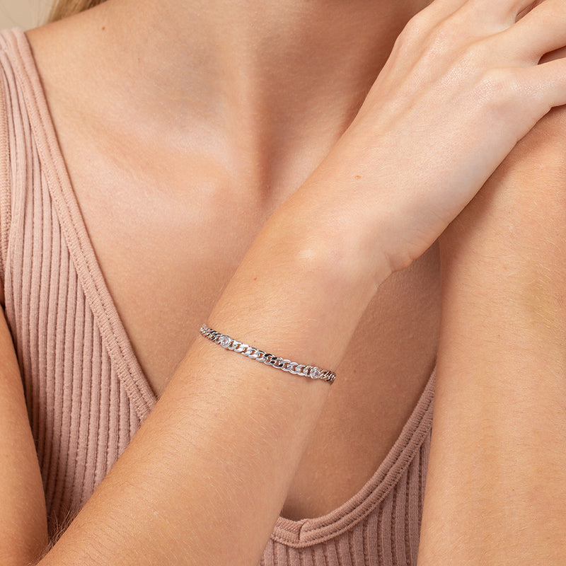 Model wearing rhodium-plated curb chain bracelet with round cubic zirconia