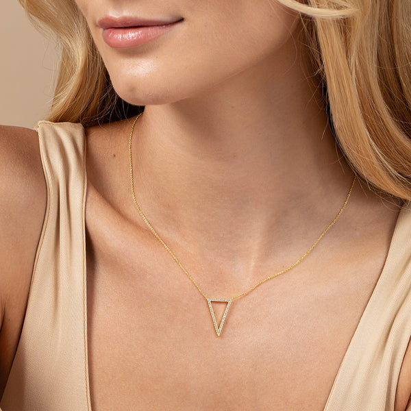 Model wearing chain necklace with an inverted triangle at its center, lined with cubic zirconia