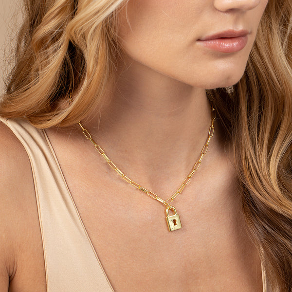 Model wearing a paper link chain necklace with lock-shaped pendant in 14k gold plating