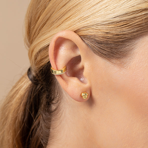 A model wearing an ear cuff plated in 14k gold with one edge lined in cubic zirconia
