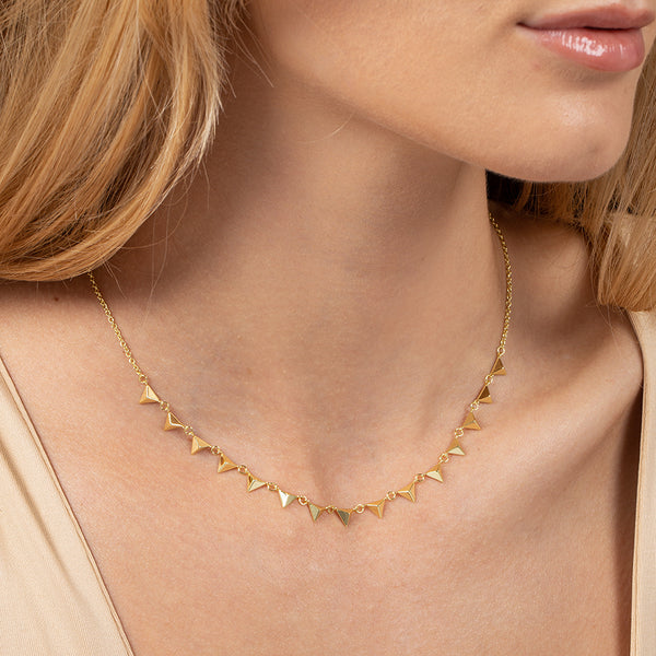 A model wearing a short length necklace plated in 14k gold with 3D triangles lined across the front