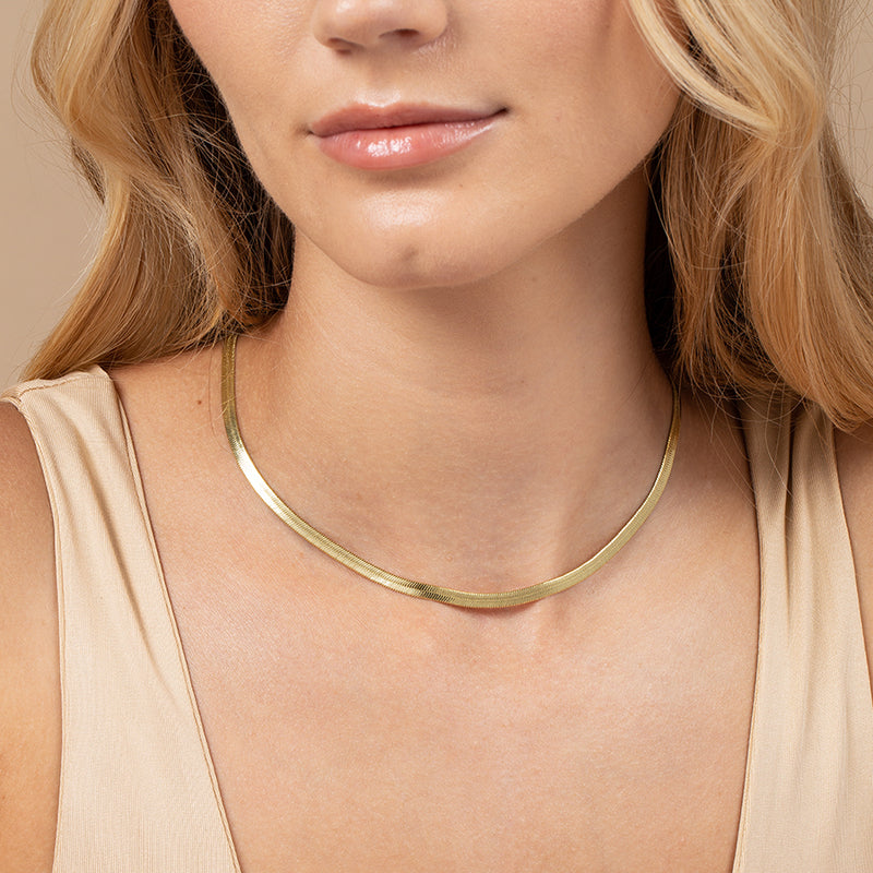 A model wearing a choker necklace created with 14k gold-plated herringbone chain