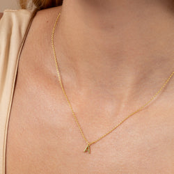 Model wearing 14k gold-plated necklace with letter A at its center