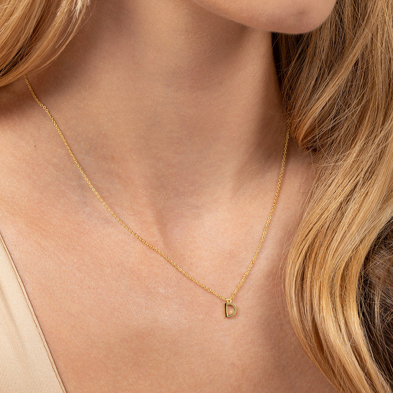 Model wearing 14k gold-plated necklace with letter D at its center
