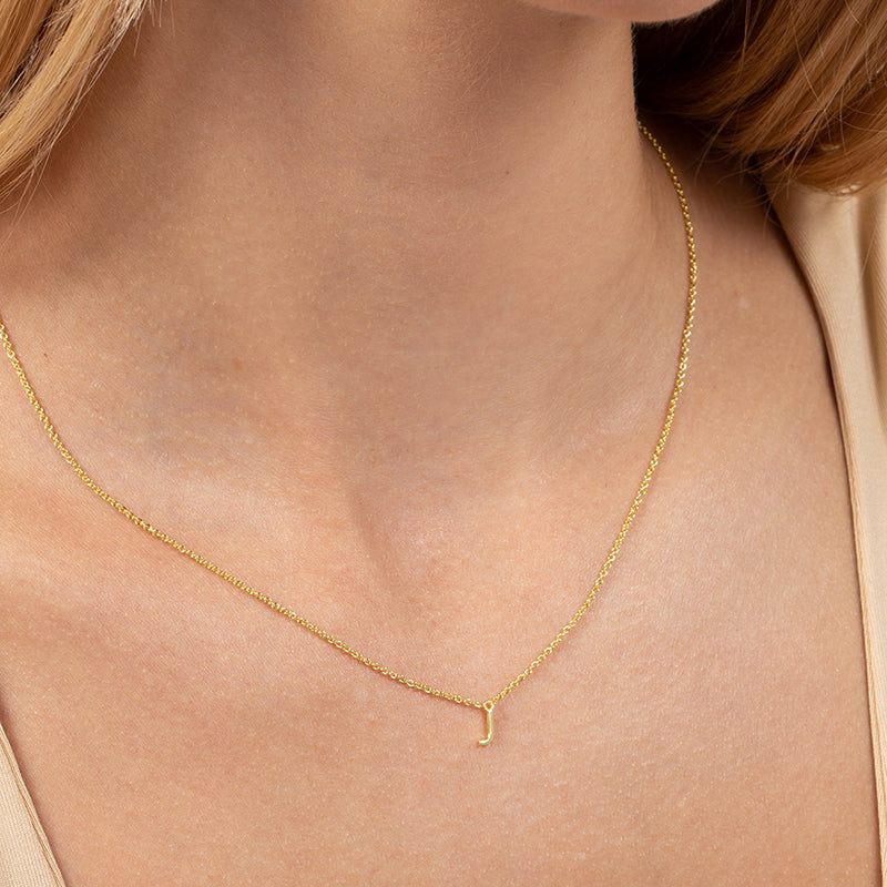 Model wearing 14k gold-plated necklace with letter J at its center