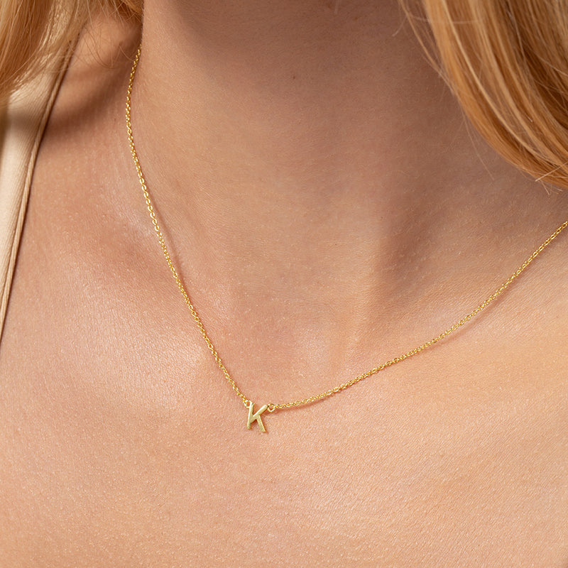 Model wearing 14k gold-plated necklace with letter K at its center