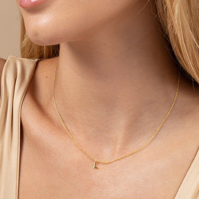 Model wearing 14k gold-plated necklace with letter L at its center