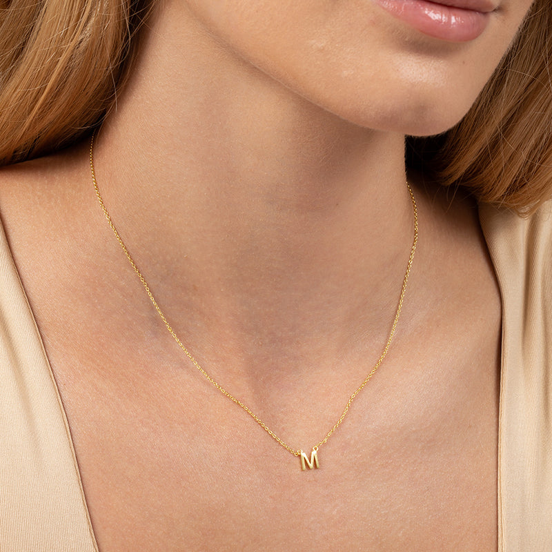 Model wearing 14k gold-plated necklace with letter M at its center