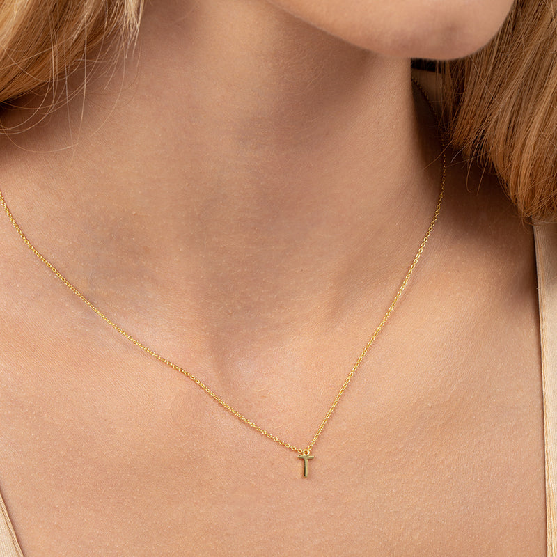 Model wearing 14k gold-plated necklace with letter T at its center