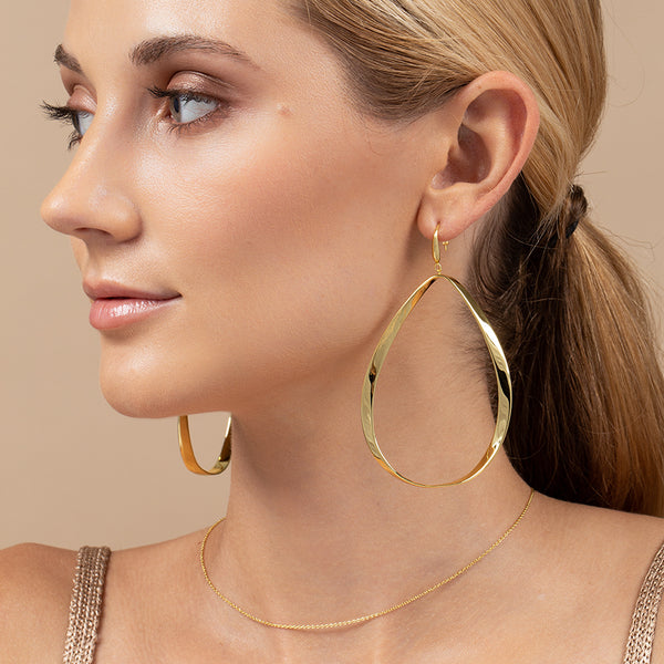 A model wearing large teardrop hoops created with 14k gold plating