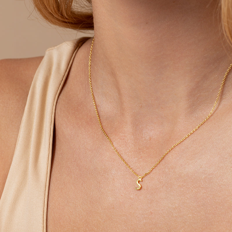 Model wearing 14k gold-plated necklace with letter S at its center