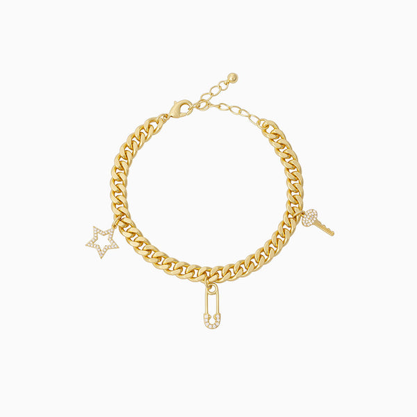 A charm bracelet featuring a studded star, safety pin, and key on a thick curb chain