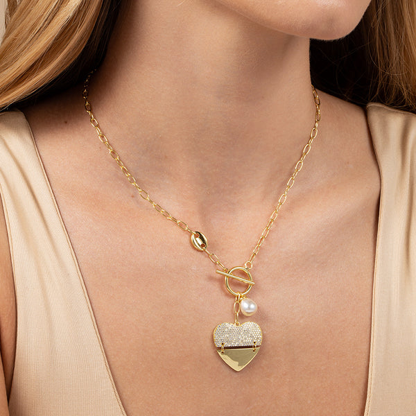 Model wearing chain necklace with large heart pendant, pearl charm, and T-bar closure plated in 14k gold