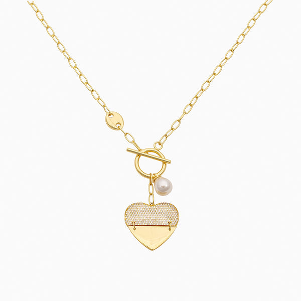 Chain necklace with large heart pendant, pearl charm, and T-bar closure plated in 14k gold