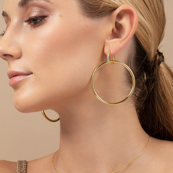 A model wearing a 14k gold-plated hoop dangling from a smaller huggie lined with cubic zirconia