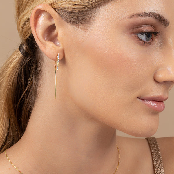 Model wearing 14k gold-plated earrings with earwire that continues past lobe for ear jacket style