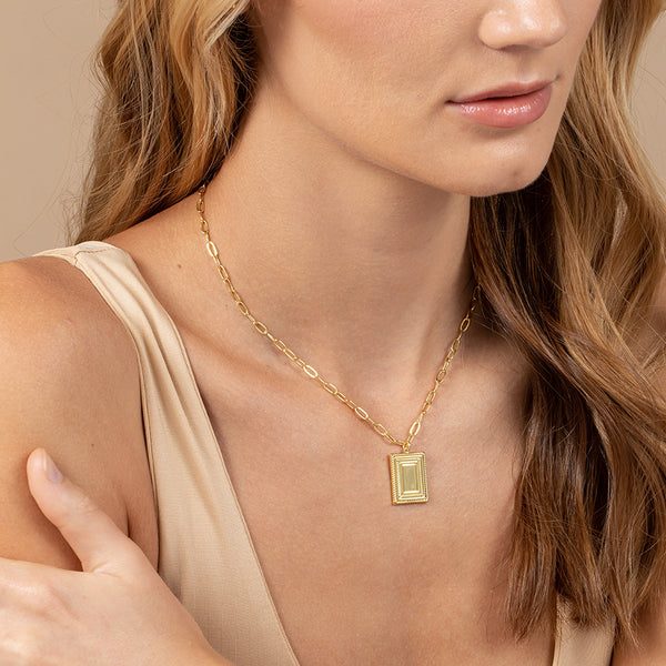 A model wearing a paper link chain necklace with ornate rectangle pendant decorated like a frame
