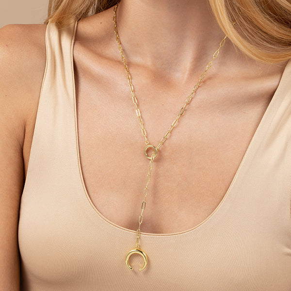 A model wearing a paper link chain necklace plated in 14k gold with crescent pendant and toggle, T-bar closure
