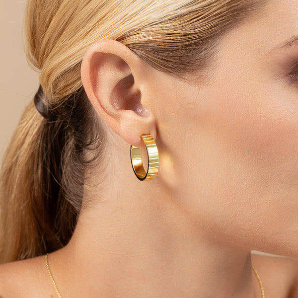 Model wearing 14k gold-plated hoop earring line with embedded horizontal lines for texture