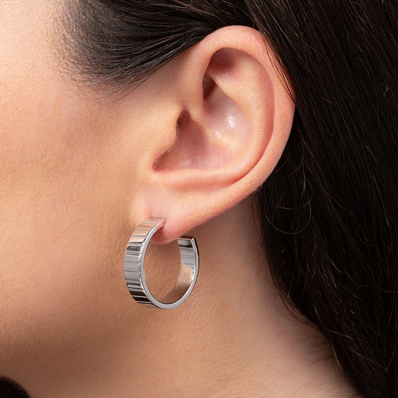Close-up of model wearing rhodium-plated hoop earring line with embedded horizontal lines for texture