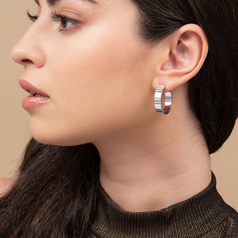 Model wearing rhodium-plated hoop earring line with embedded horizontal lines for texture