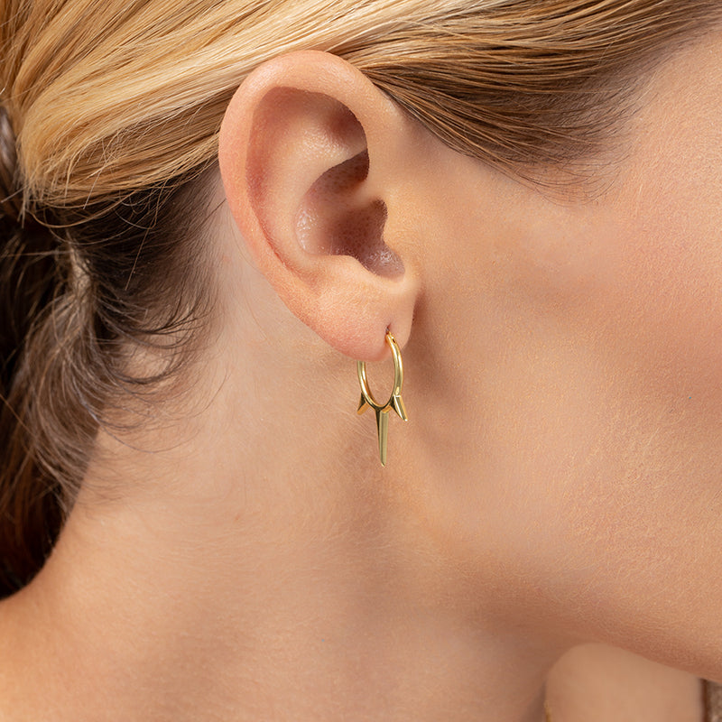 A model wearing small huggie-style hoops with 3 spikes, plated in 14k gold