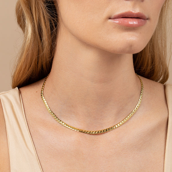 A model wearing a women's cuban chain necklace plated in 14k gold