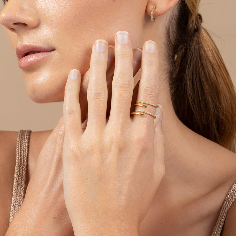A model wearing a 14k gold-plated ring with 4 alternating bands, created with cubic zirconia
