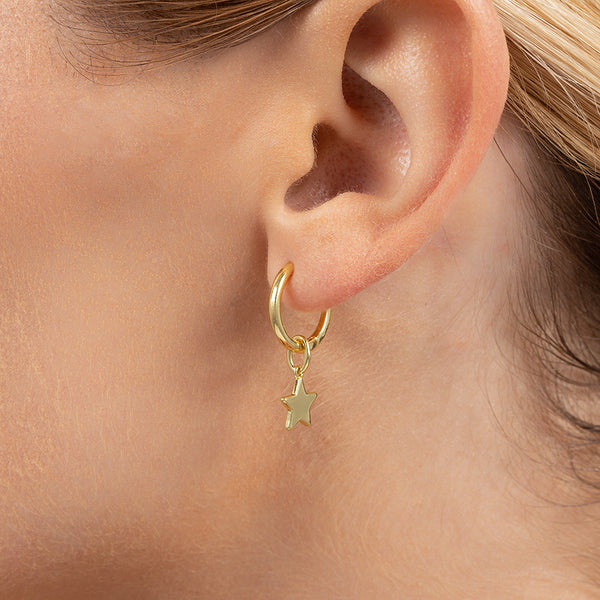A model wearing a 14k gold-plated charm shaped like a star, hanging on a small hoop