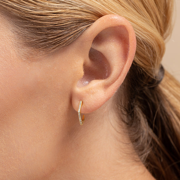A model wearing Huggie earrings with a hexagon shape, lined with cubic zirconia