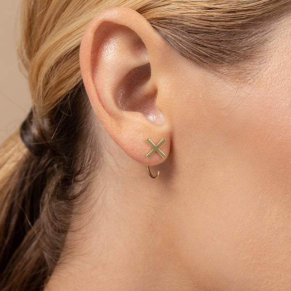 A model wearing X-shaped earrings with ear jacket style, plated in 14k gold