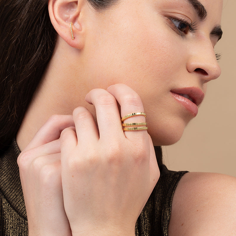 A model wearing 3 matching rings plated in 14k gold with engraved lines for texture