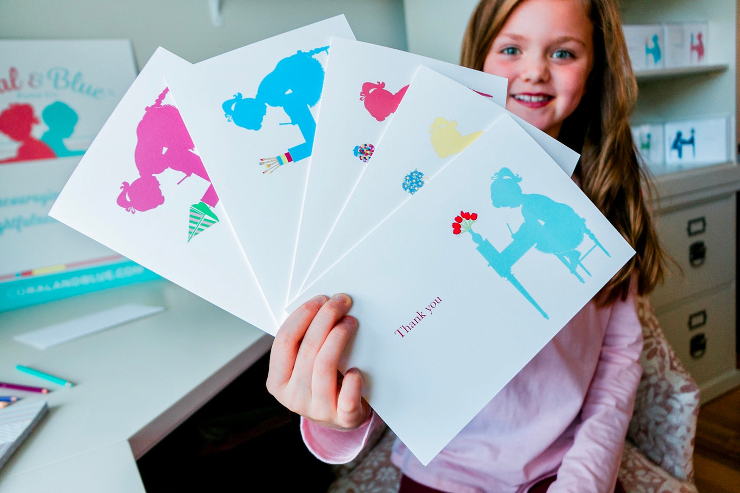 Happy child holding Coral and Blue Paper, Co. stationery for kids. Made in the USA. Saratoga Springs, NY.