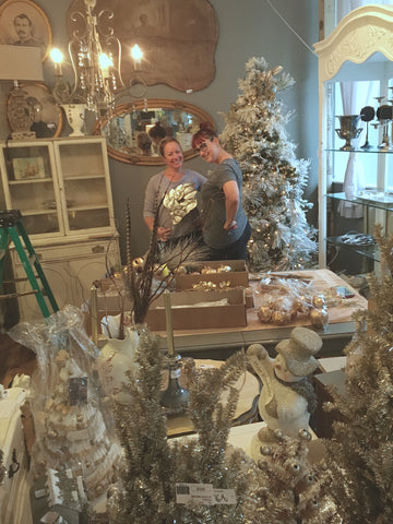 Abbey Lemmons and Claire LeGrand setting up silver and gold Christmas tree at The White Rabbit