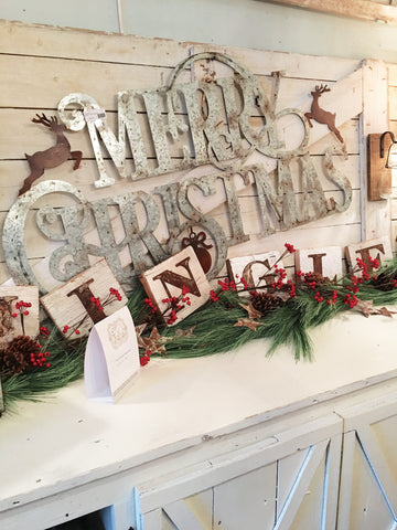 "Buffet decorated with large Merry Christmas sign and wood letter blocks spelling out ""jingle"""